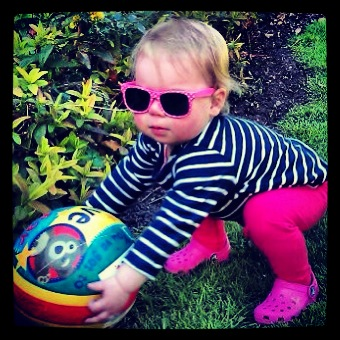 Baby in the spring garden wearing sunglasses and holding a ball