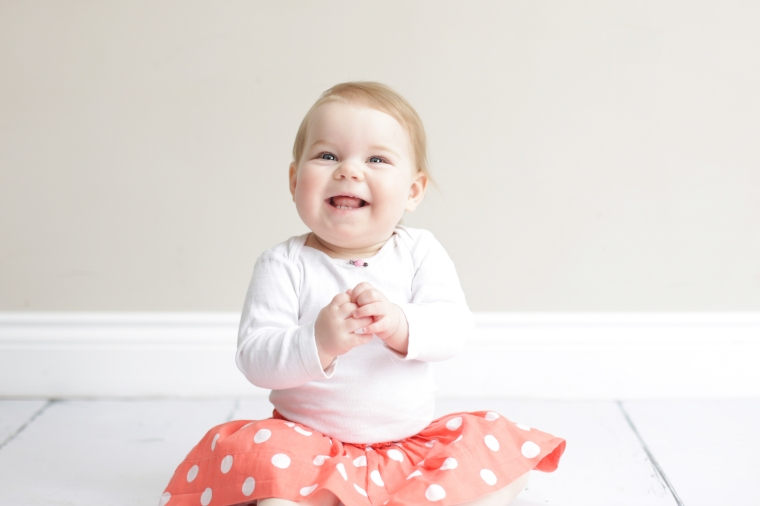 Smiling baby in orange polka=dot skirt