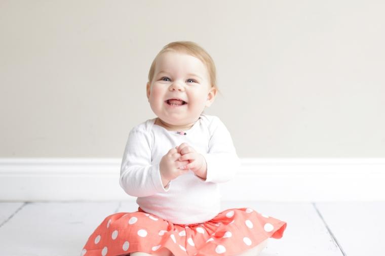Smiling baby in orange polka=dot skirt