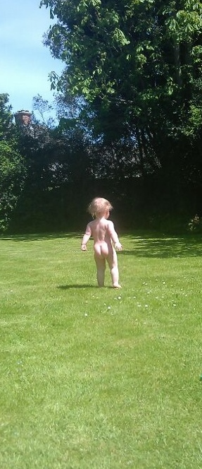 naked baby on green grass lawn